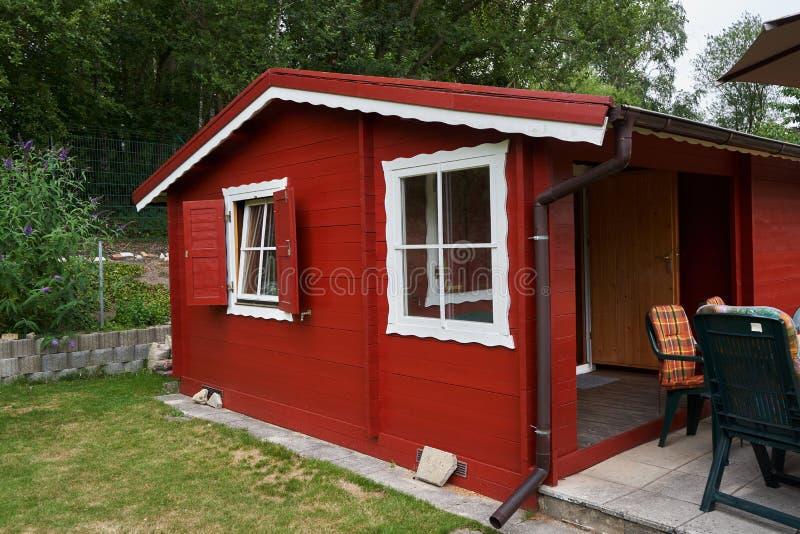 Klein rood geschilderd tuinhuis met terras stock foto