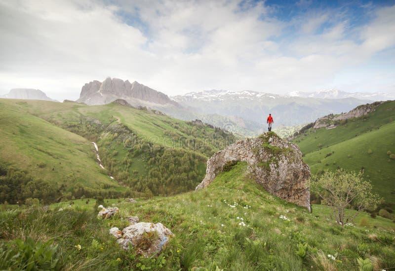 Klein silhouet van reiziger bovenop rots royalty-vrije stock foto's