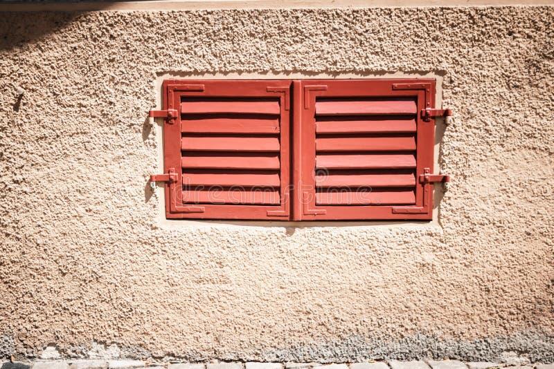 Klein venster met rode gesloten blinden royalty-vrije stock afbeelding