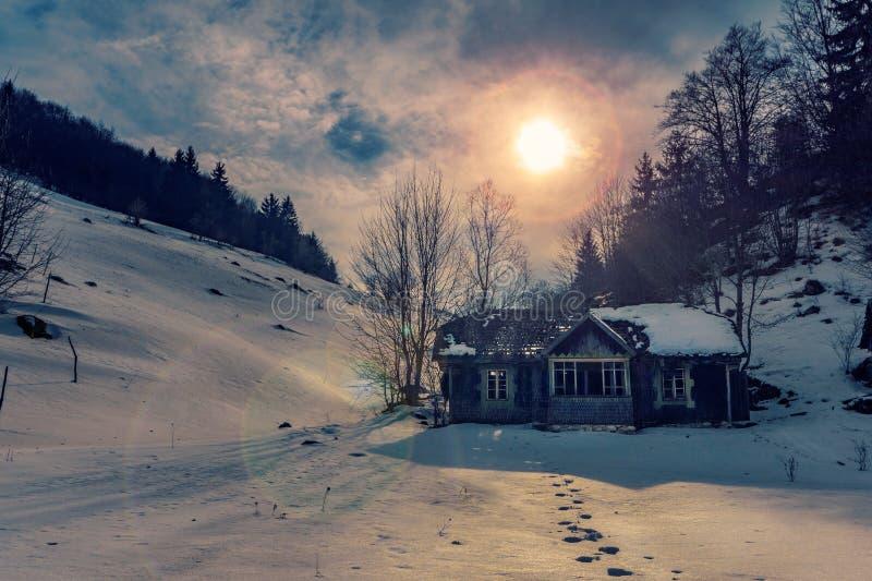 Klein verlaten huis dat op de heuvels met footstepts in sneeuw het leiden aan het huis wordt gevonden dat in de bergen op de zonn stock fotografie