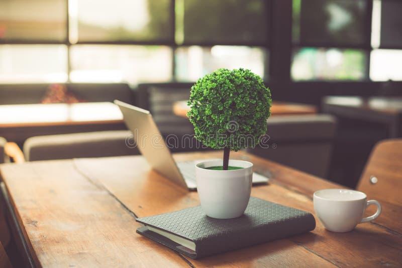 Klein verzieren Sie Baum, Laptop, Notizbuch und Kaffeetasse herein auf Holztisch in der Kaffeestube Mit-arbeitender Raum des Ents lizenzfreies stockfoto