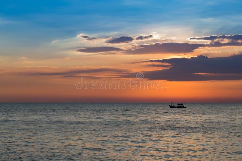 Klein visserijschip over de horizon van de zonsondergangzeekust royalty-vrije stock foto
