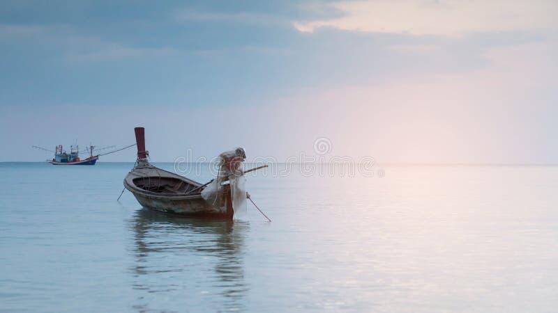 Klein vissersbootparkeren op oceaanhorizon stock fotografie