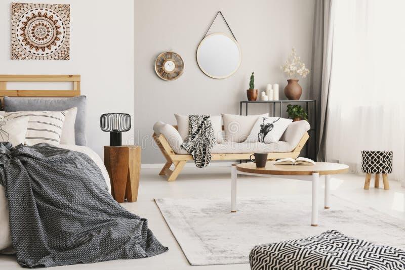 Klein vlak die binnenland met bed, venster, koffietafel met mok en boek op tapijt, zitkamer met deken wordt geplaatst en royalty-vrije stock afbeeldingen