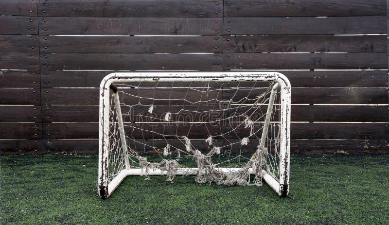 Klein voetbaldoel met oude netto in de speelplaats voor kinderen stock foto