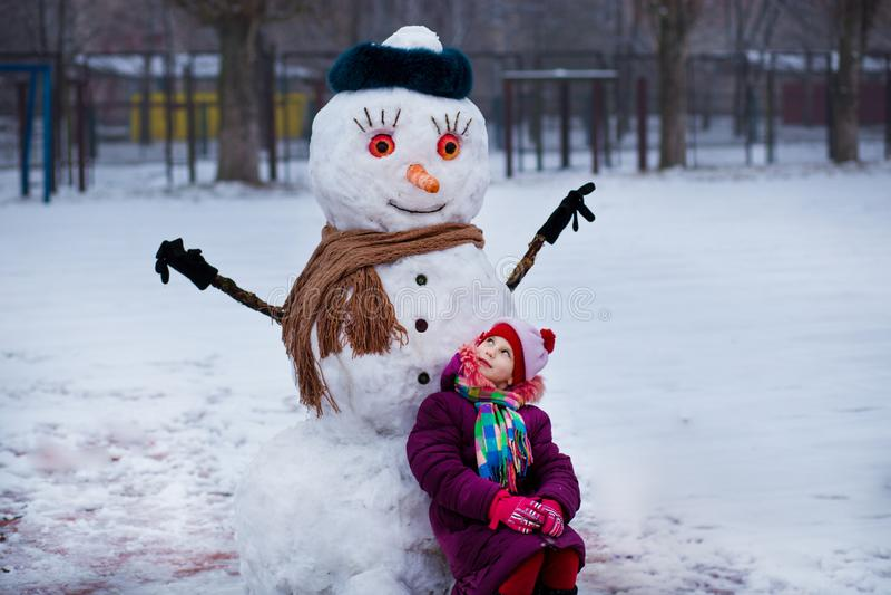 Klein vrolijk meisje dichtbij grote grappige sneeuwman Het leuke meisje heeft pret in de winterpark royalty-vrije stock fotografie