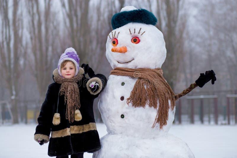 Klein vrolijk meisje dichtbij grote grappige sneeuwman Het leuke meisje heeft pret in de winterpark royalty-vrije stock afbeelding