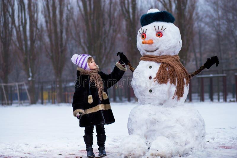 Klein vrolijk meisje dichtbij grote grappige sneeuwman Het leuke meisje heeft pret in de winterpark stock fotografie