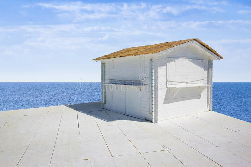 Klein wit houten plattelandshuisje met met stro bedekt dak door het overzees - beeld met exemplaarruimte royalty-vrije stock foto