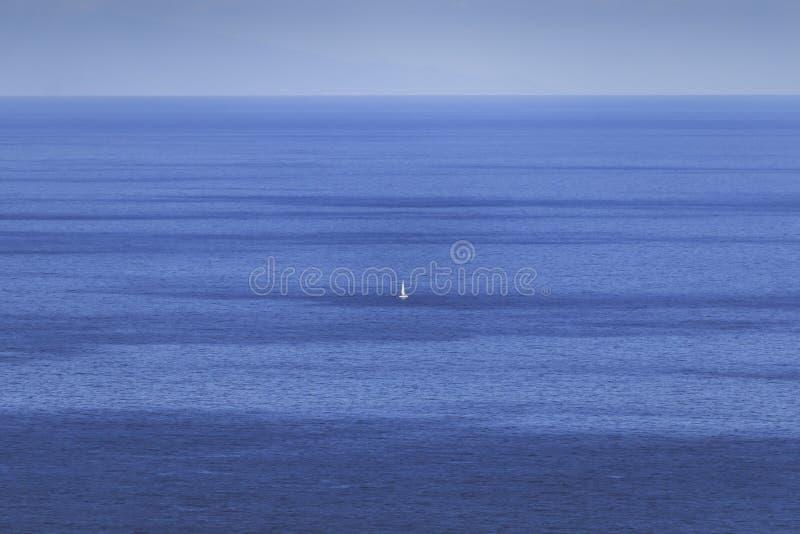 Klein wit schip in midle van de kalme Atlantische Oceaan royalty-vrije stock foto's