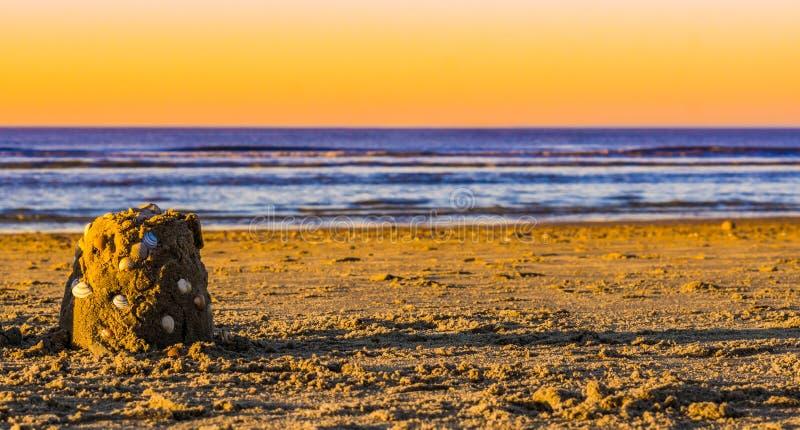 Klein zandkasteel dat met zeeschelpen op het strand bij zonsondergang wordt verfraaid, mooie blauwe oceaan met een kleurrijke hem stock foto