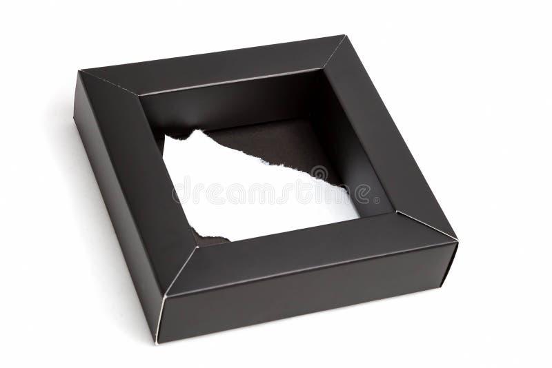 Klein zwart kartonvakje met een leeg binnen blad van document Voor een witte ge?soleerde achtergrond, stock fotografie
