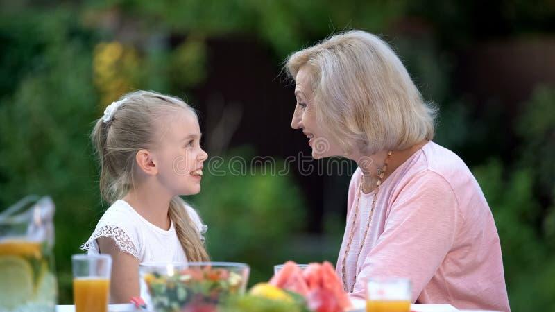 Kleindochter die grappig verhaal vertellen aan grootmoeder, generatiebrug, liefde royalty-vrije stock afbeelding