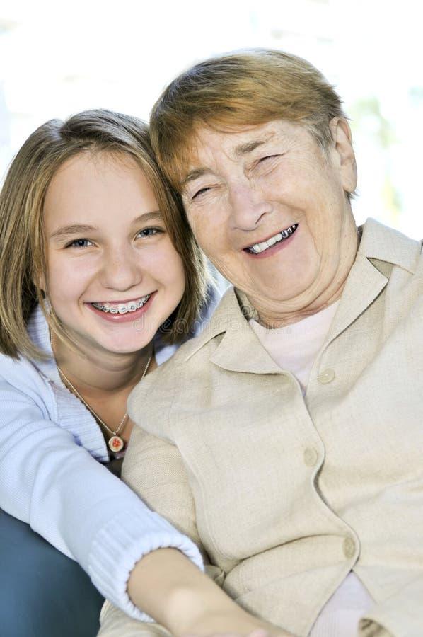 Kleindochter die grootmoeder koestert stock foto's