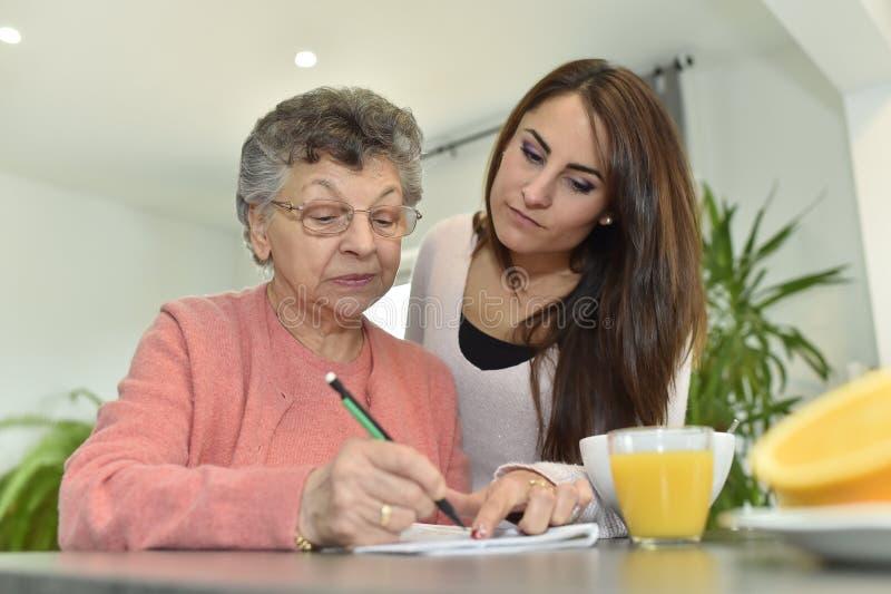 Kleindochter die haar grootmoeder in pensioneringshuis bezoeken stock fotografie