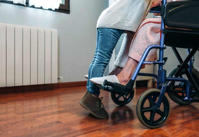Kleindochter die haar grootmoeder in rolstoel bezoeken royalty-vrije stock fotografie
