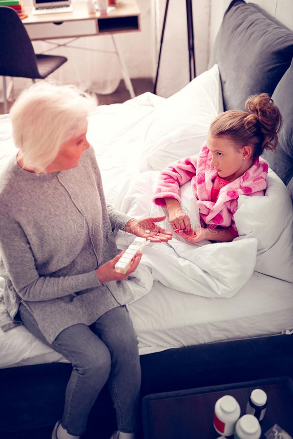 Kleindochter die het droevige liggen in bed en het spreken voelen aan oma royalty-vrije stock fotografie