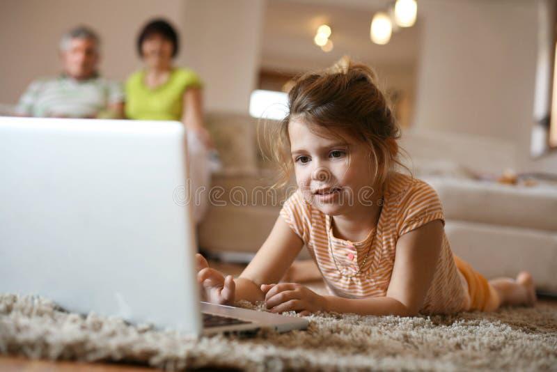 Kleindochter die laptop in woonkamer met behulp van royalty-vrije stock afbeeldingen