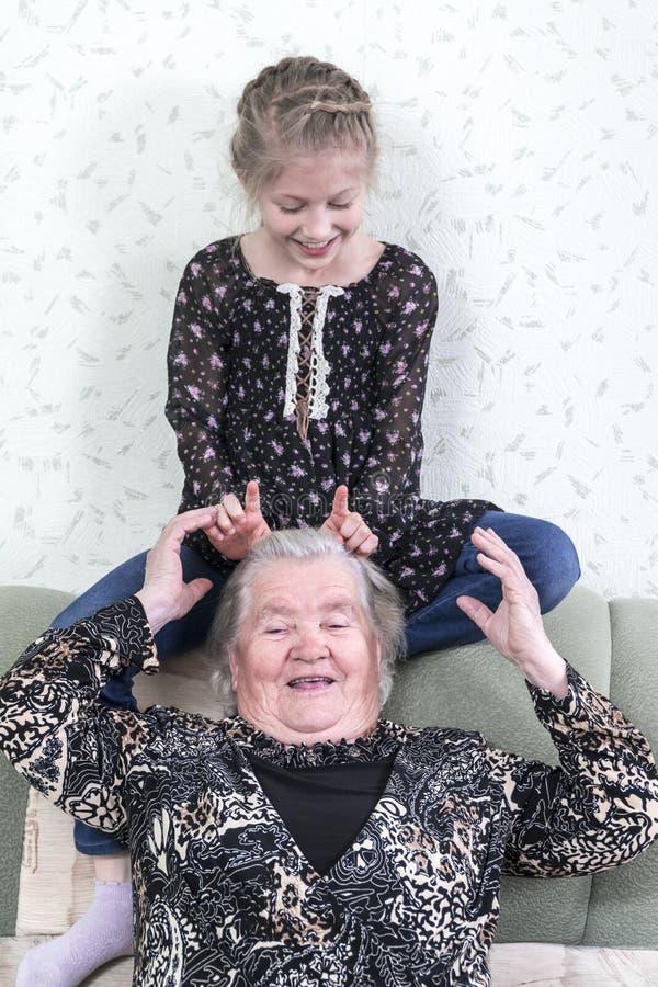 Kleindochter die tot hoornen maken aan grootmoeder royalty-vrije stock afbeelding