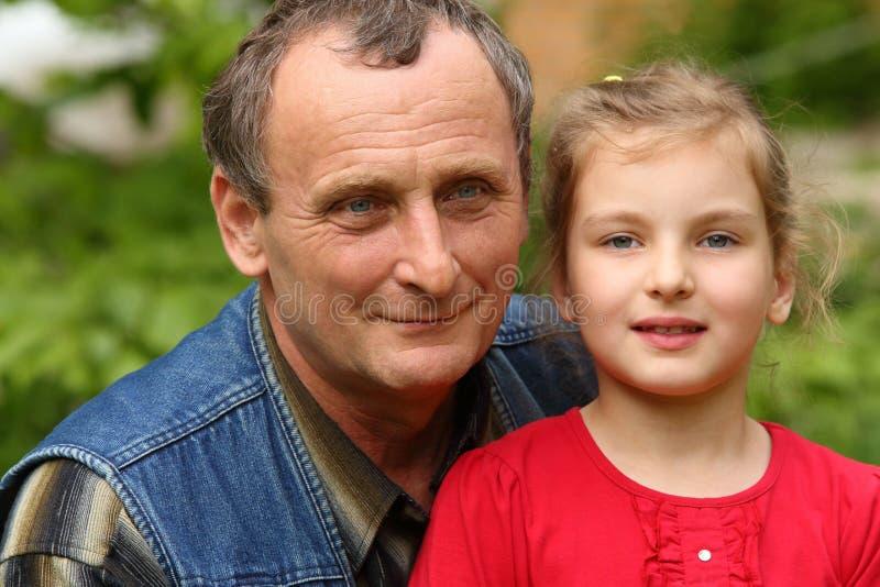 Kleindochter in een rode kleding met haar grootvader royalty-vrije stock afbeeldingen