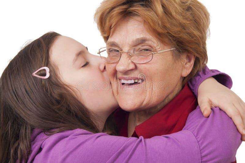 Kleindochter kussende grootmoeder royalty-vrije stock foto
