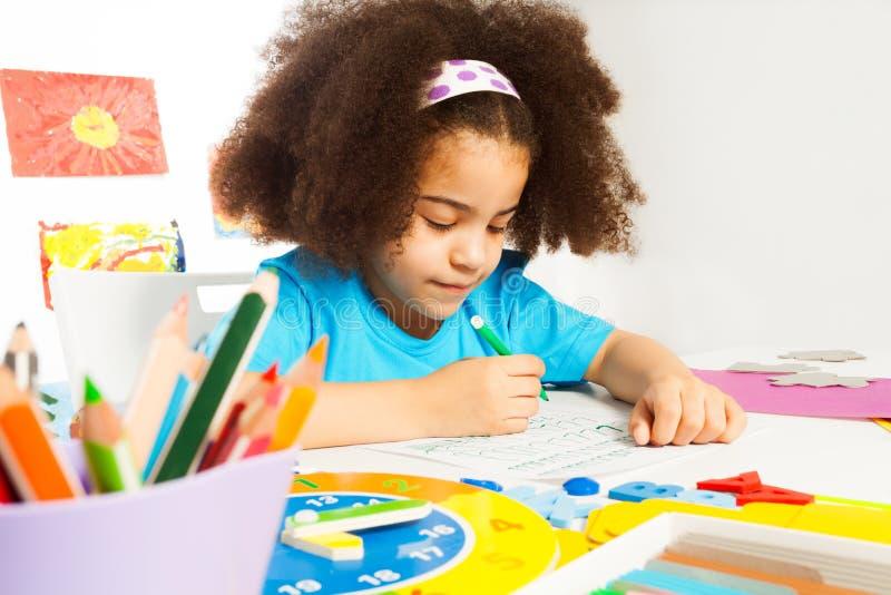 Kleine Afrikaanse meisje het schrijven brieven op het document royalty-vrije stock fotografie