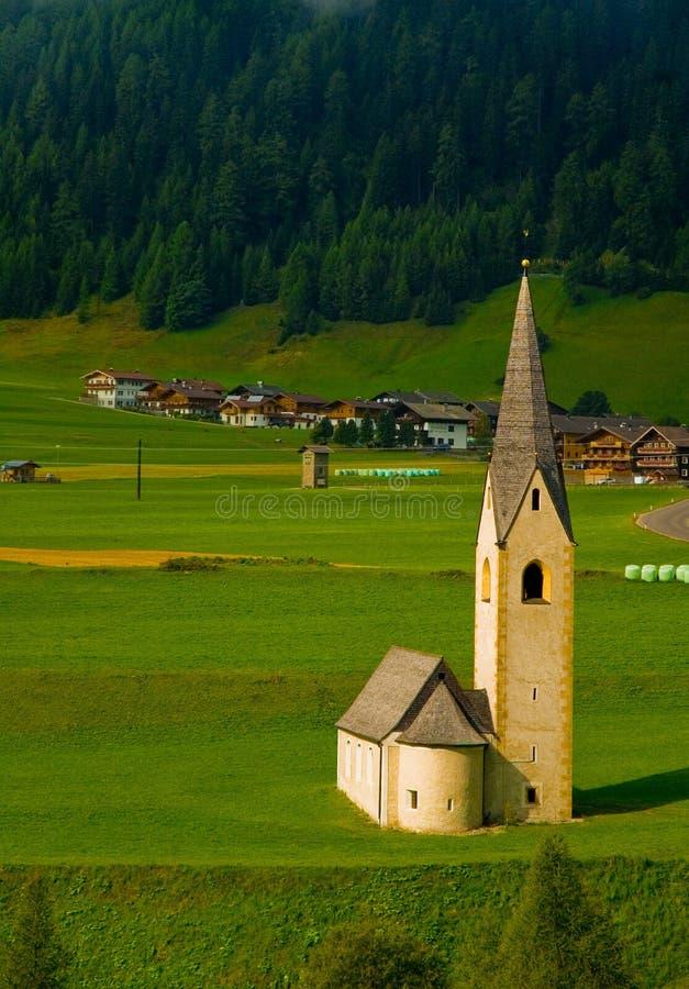 Kleine alpine Kirche auf dem grünen Gebiet stockbilder