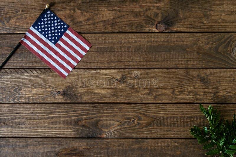 Kleine amerikanische Flagge mit Farn auf gealtertem, verwittertem rustikalem hölzernem Hintergrund lizenzfreie stockfotografie
