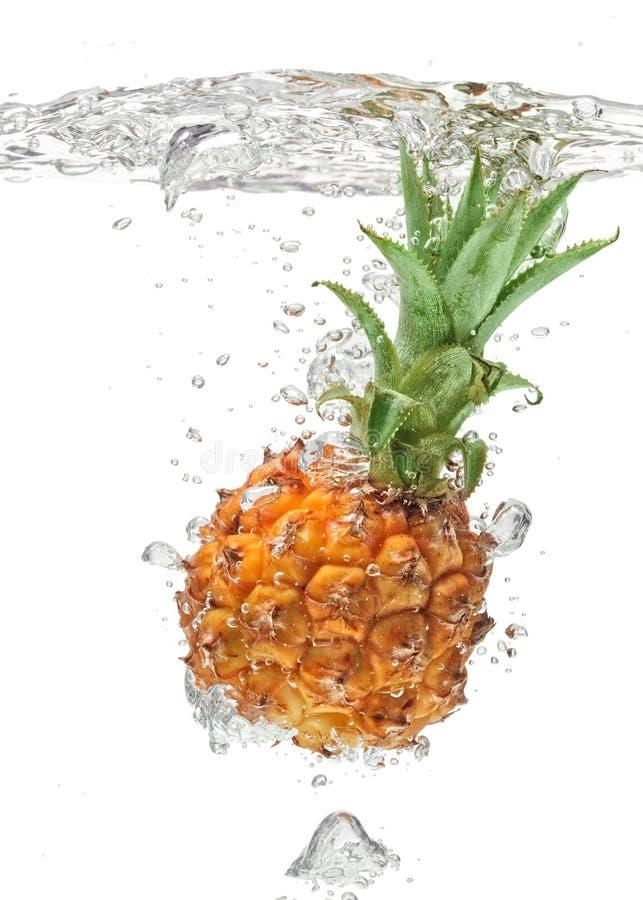 Kleine ananas die in water op wit valt stock fotografie