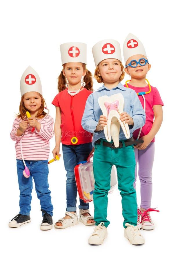 Kleine artsen met tandmodel en stuk speelgoed instrumenten stock foto's