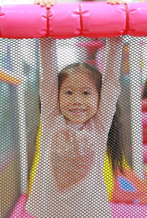 Kleine asiatische Kindermädchenrückseite ein Netz, das zuhause im Spielplatz spielt und hängt Aktives M?dchen, das Spa? im Sportz lizenzfreies stockfoto