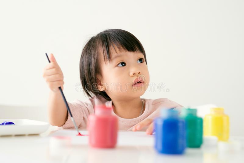 Kleine asiatische Mädchenmalerei mit Malerpinsel und bunten Farben stockfotos