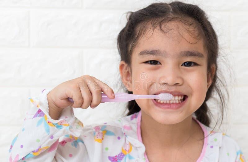 Kleine asiatische nette Mädchenbürstenzähne lizenzfreie stockbilder