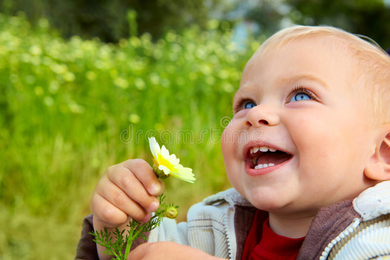 Kleine baby die met madeliefje lacht stock foto