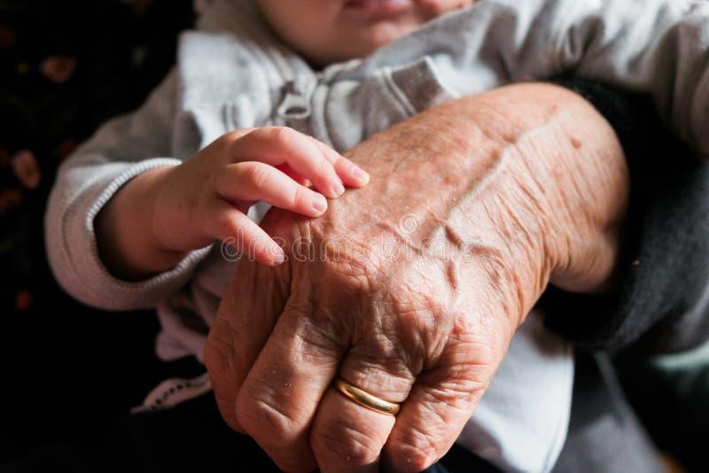 Kleine babyhand die en oude grootmoederhand met rimpels raken strelen, symbool van het overgaan van generaties stock fotografie