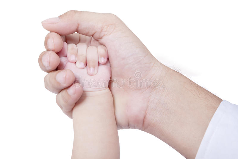Kleine babyhand op de vaderpalm stock foto's