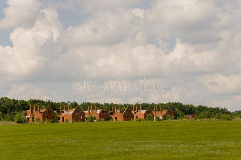 Kleine Backsteinhäuser der orange Farbe im Vorort Grünes Gras und Bäume herum Vor Regen dorf stockfoto