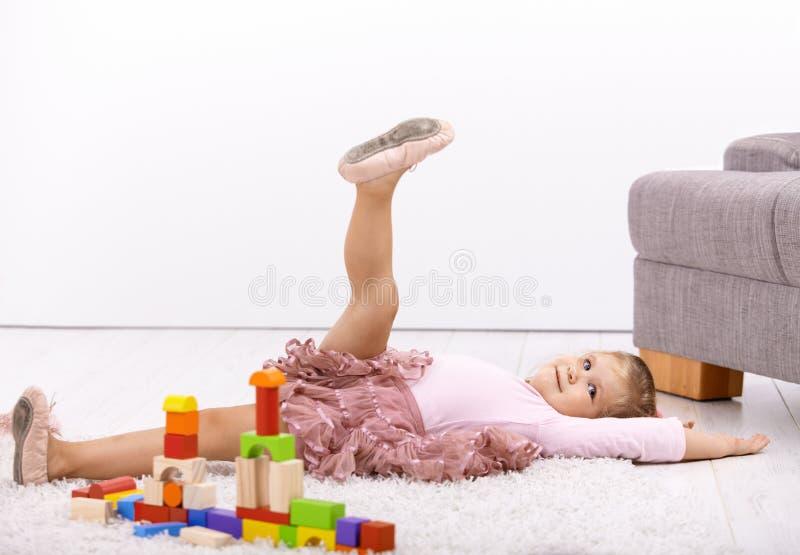 Kleine Ballerina, die auf Fußboden aufwirft lizenzfreie stockfotos