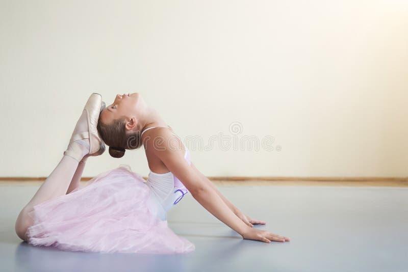 Kleine Ballerina, die vor Leistung in der Ballettklasse ausdehnt stockfoto
