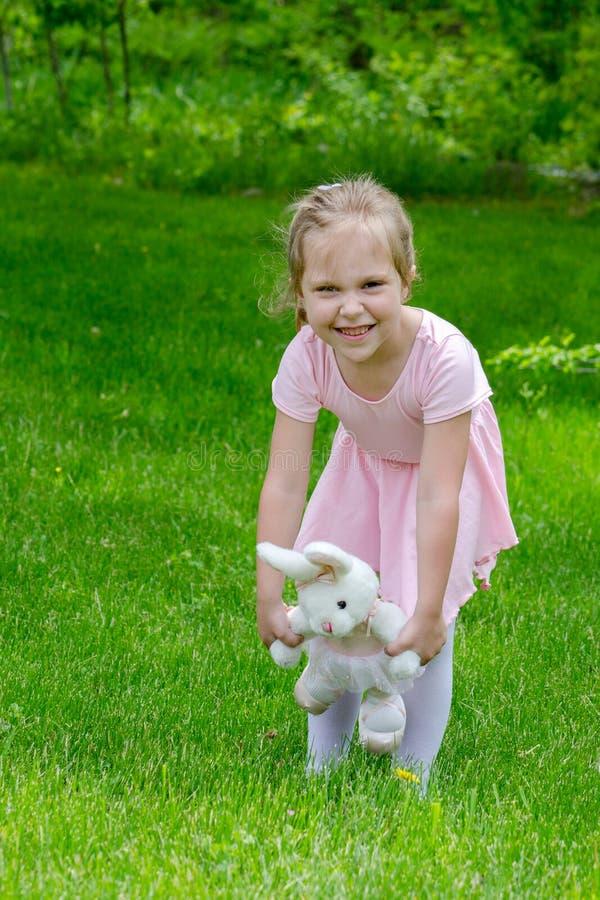 Kleine Ballerina mit Spielzeughäschen stockbilder