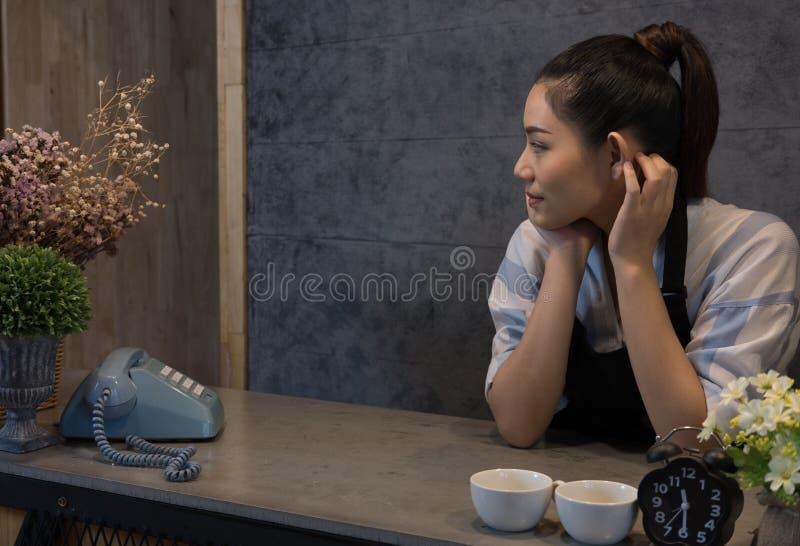 kleine bedrijfseigenaar bij haar koffiewinkel gelukkige Aziatische vrouwentribune stock fotografie