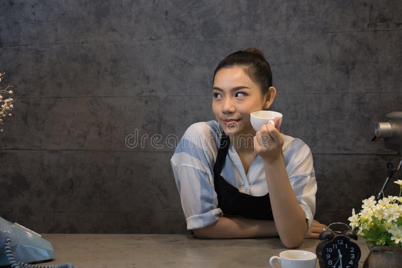 kleine bedrijfseigenaar bij haar koffiewinkel gelukkige Aziatische vrouwentribune stock afbeelding
