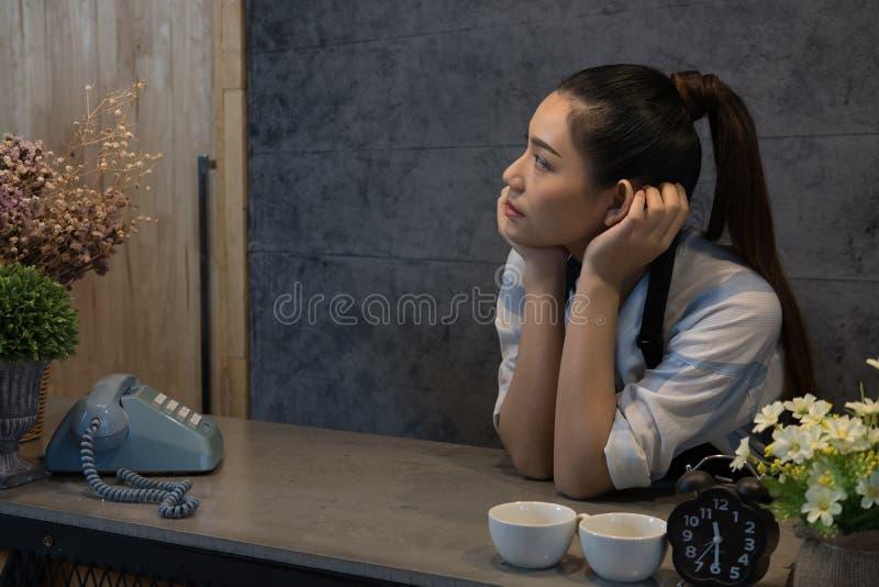 kleine bedrijfseigenaar bij haar koffiewinkel gelukkige Aziatische vrouwentribune royalty-vrije stock afbeelding