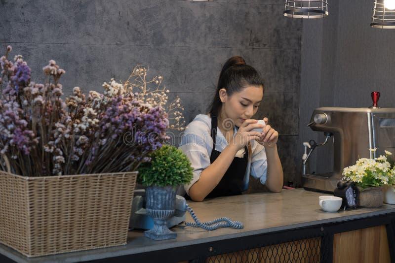kleine bedrijfseigenaar bij haar koffiewinkel gelukkige Aziatische vrouwentribune royalty-vrije stock afbeeldingen