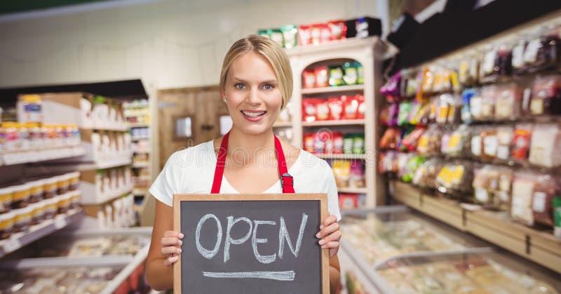 Kleine bedrijfseigenaar die een klein bord met het open woord houden stock foto's