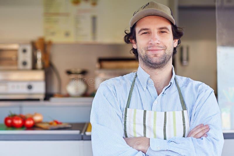 Kleine bedrijfseigenaar die voor zijn meeneemvoedselbusin glimlachen royalty-vrije stock fotografie