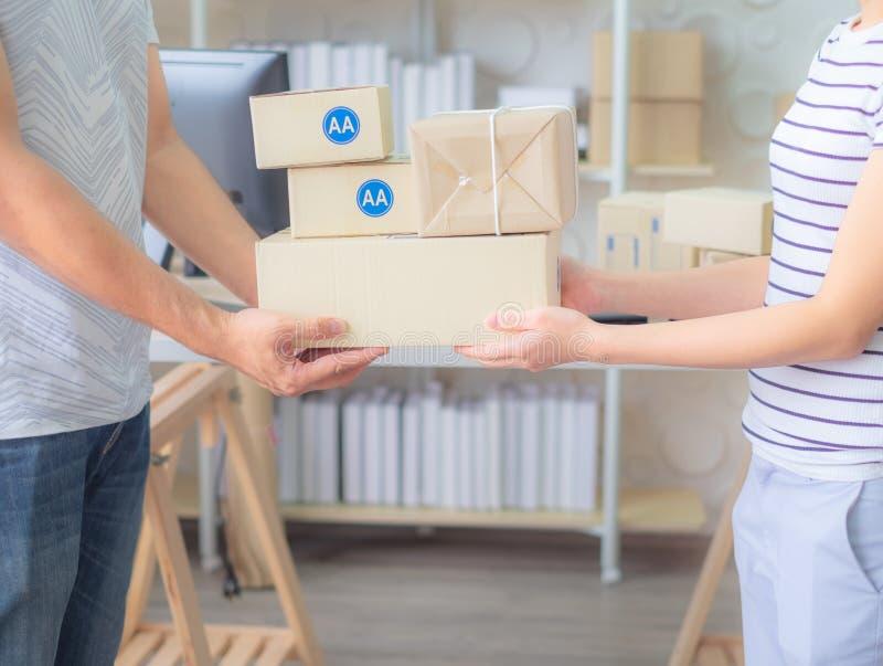 Kleine bedrijfseigenaarparen Thuis het houden van ingepakt product in dozen, Klaar voor leveringsbureau stock fotografie