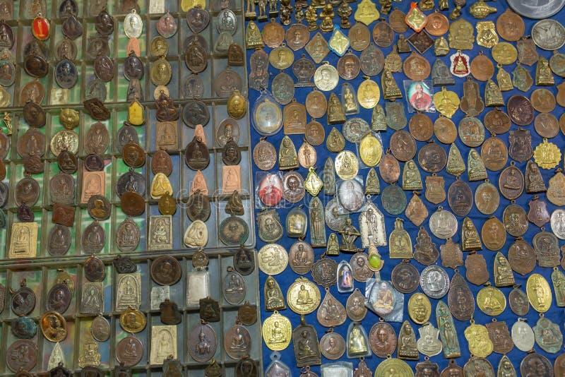 Kleine beelden van Boedha en monniken op steen en metaalamuletten voor verkoop op straatmarkt stock afbeelding