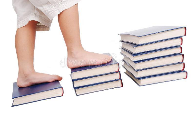 Kleine benen die op boekentreden stappen stock foto