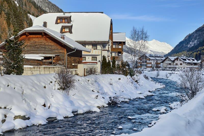 Kleine bergstroom in de Alpen van Tirol Het blokhuis dichtbij bergrivier wordt behandeld door sneeuw stock afbeelding